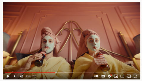 A man and a women in yellow bathrobes recline with face packs, sipping Coca-Cola through a straw