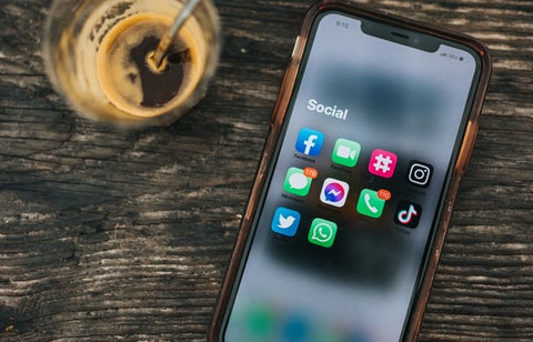 A cell phone sits next to a half drunk coffee, displaying social media icons