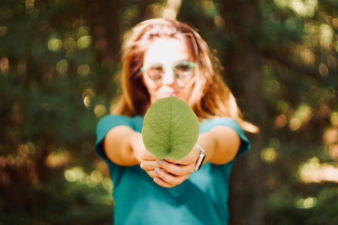 A young woman wearing sunglasses holds a big green leaf out to the camera