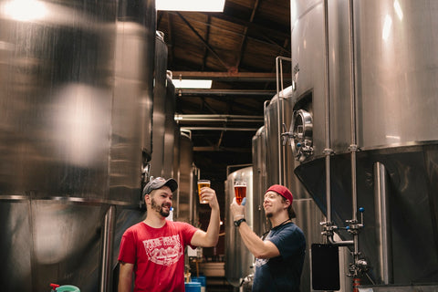 Two men raise a glass to their upstart craft beer