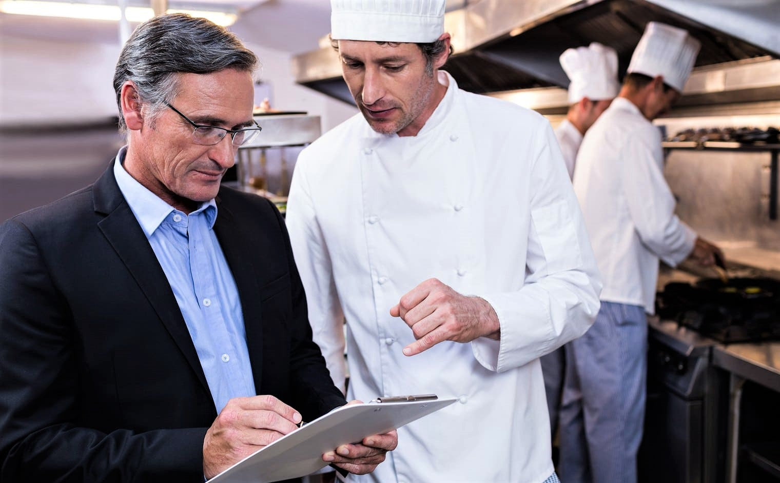 well-dressed manager in suit speaks to chef in white hat of successful restaurant