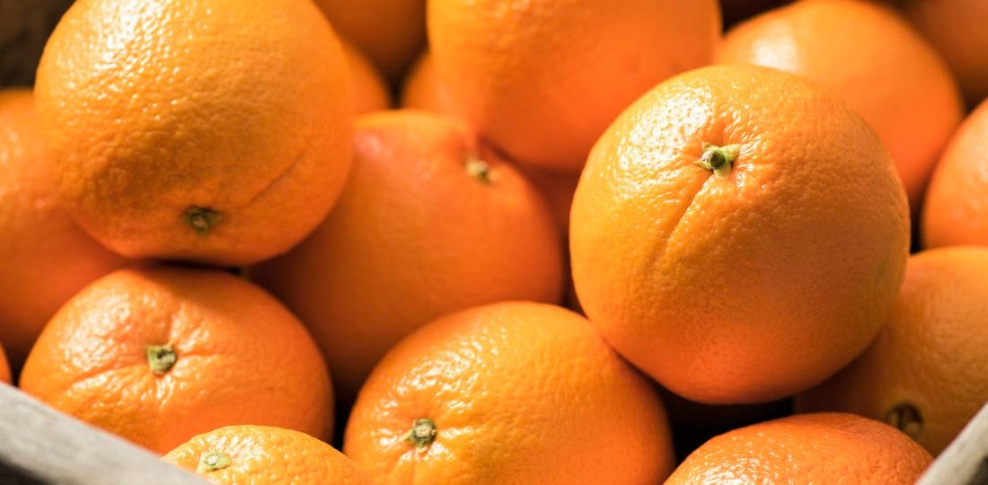 large wooden crate full of bright navel oranges