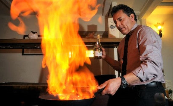 chef uses flaming pan in dynamic action shot cooking in restaurant kitchen