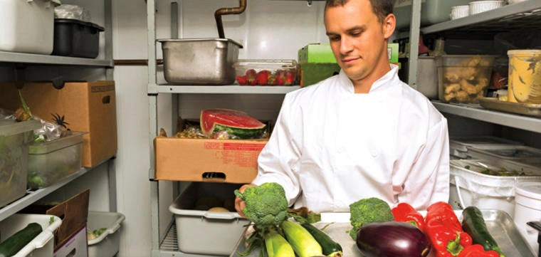 handsome young chef calculates food costs in restaurant larder