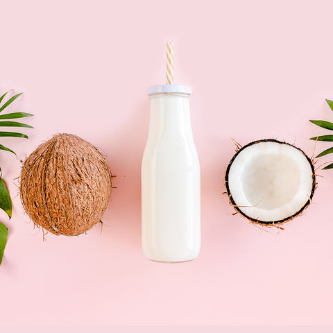 A bottle of coconut milk on a pink background with a cut coconut next to it