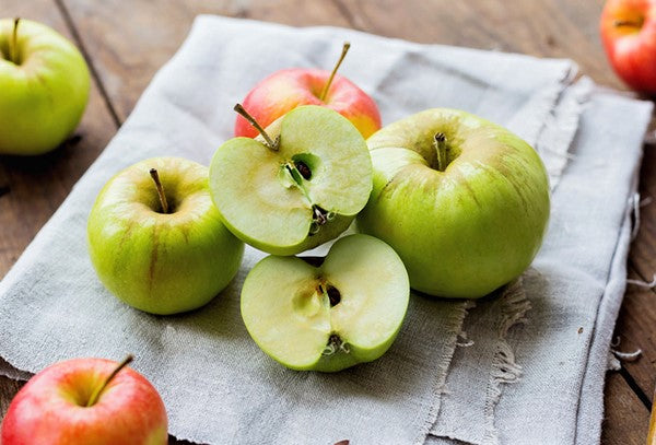 small pile of organic Granny Smith apples sliced in half