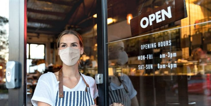 young woman in facemask stands at newly reopened restaurant during covid crisis
