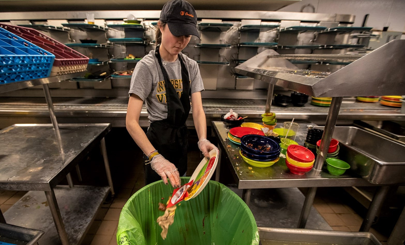 young woman scoops dead plate of food waste into restaurant bin