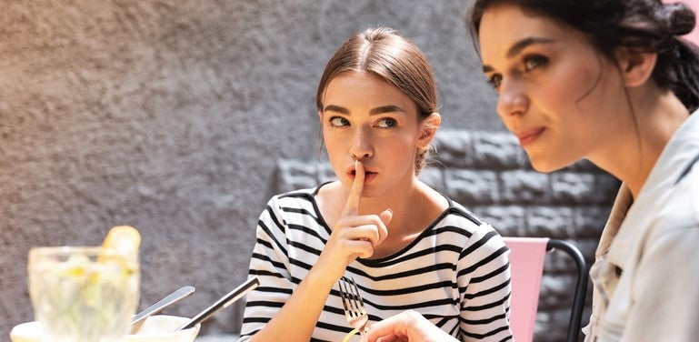 pair of young women conspiring to dine and dash in restaurant