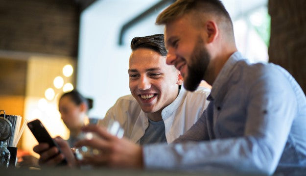 customers selecting their meal with smartphone in restaurant