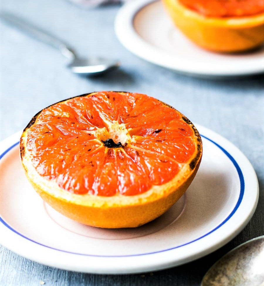 grilled grapefruit half covered in glazed brown sugar and presented on small white plate