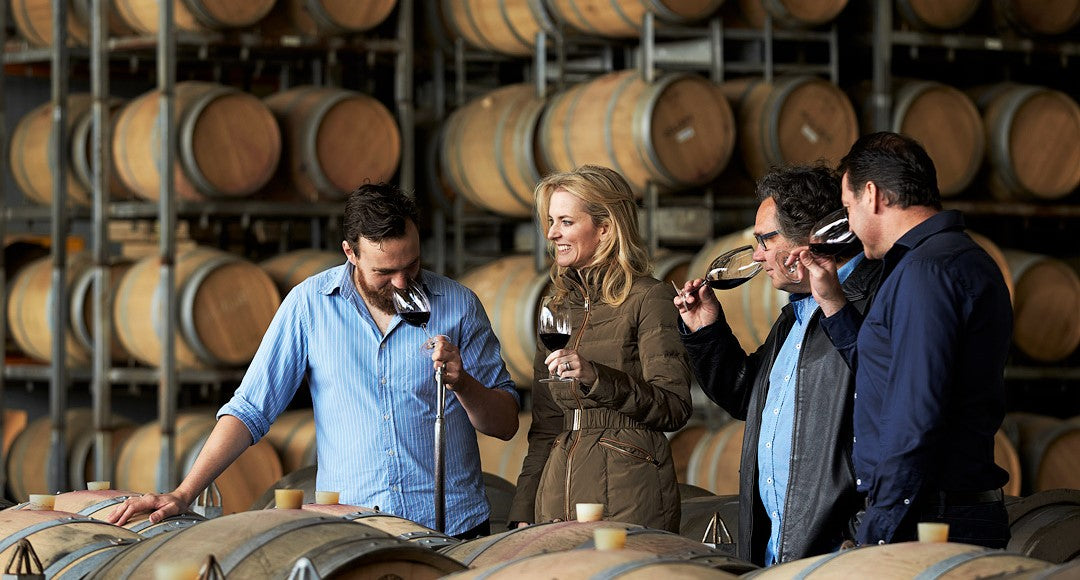 group of wine makers stand at large barrel and test out new wine