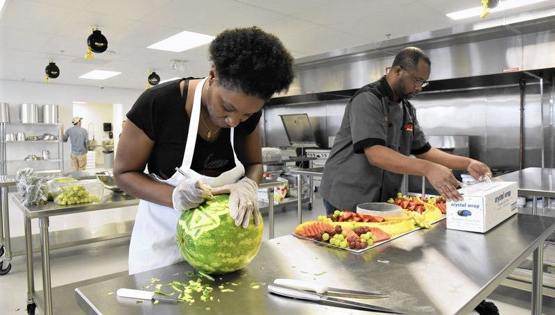 woman of color prepares organic ingredients for cooking in shared incubator kitchen