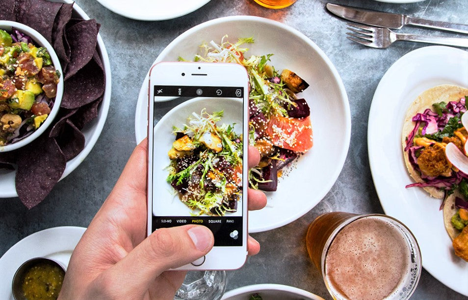 instagram influencer uses iphone to post food in restaurant
