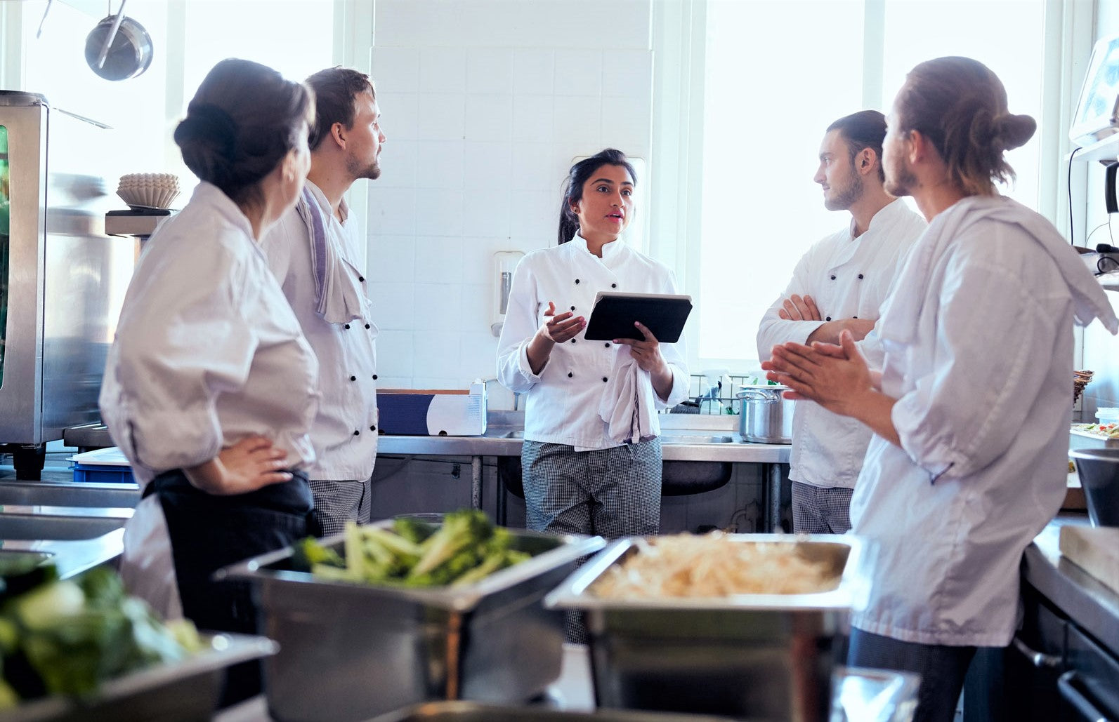 kitchen staff communicating with one another to work out to reduce food costs