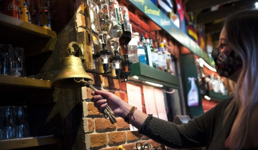 young woman behind bar rings bell for last orders in pub