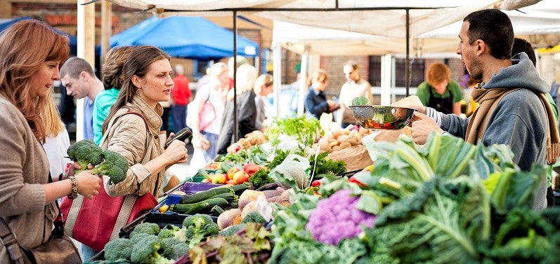 young woman purchases organic produce from man at local farmer's market