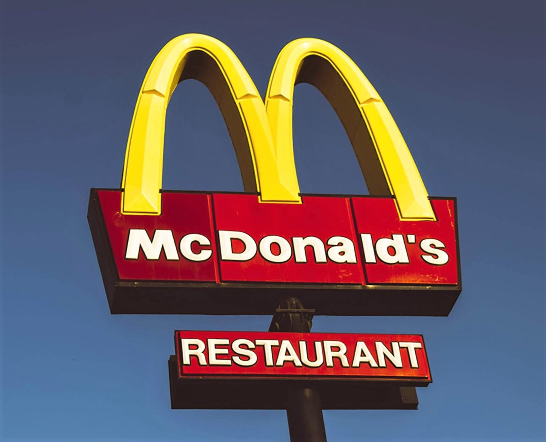 mcdonald's golden arches shining in the bright blue sky
