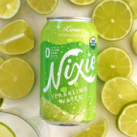 Vegan, no-GMO, gluten-free Lime Sparkling Wate, Nixie, 12 oz can in the background of limes