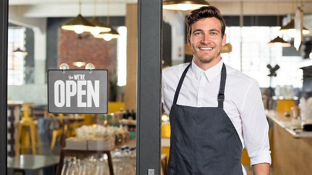 handsome young waiter in white shirt stands in newly opened restaurant