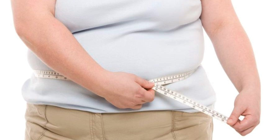 obese person measures waist wearing large white t-shirt
