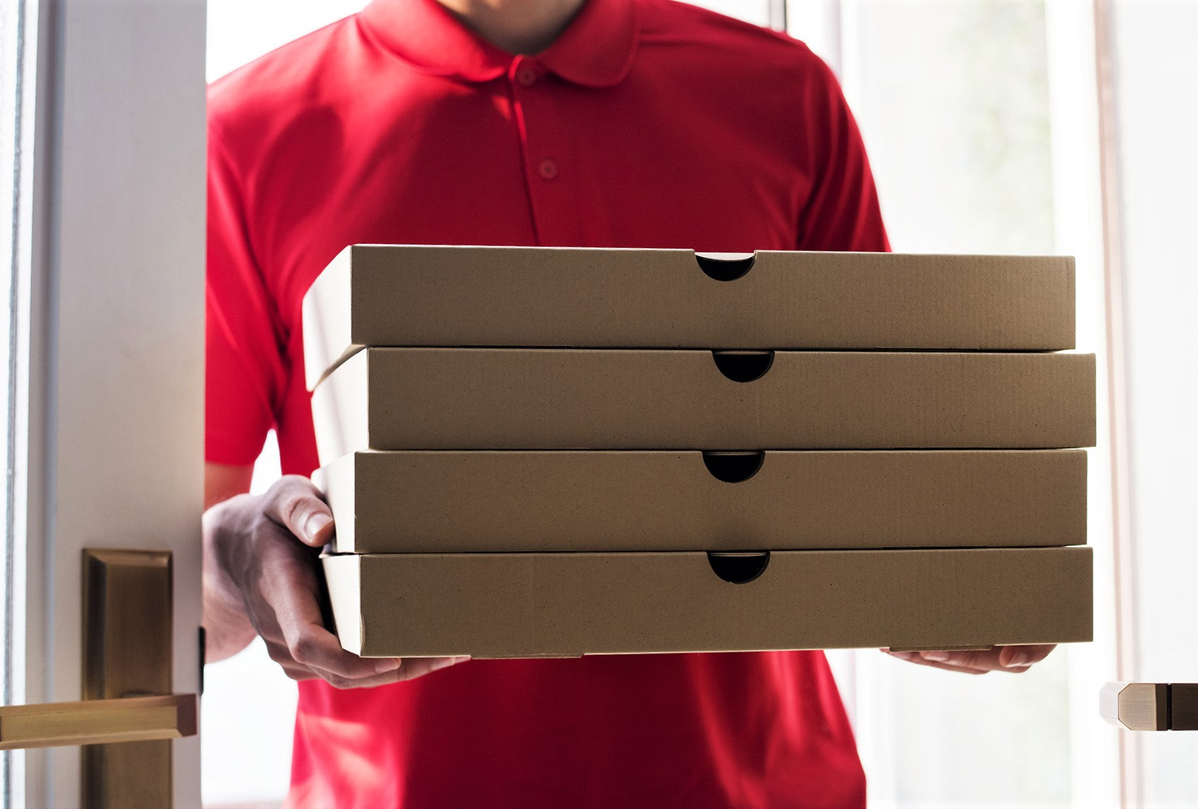 pizza delivery man in red shirt carrying stack of hot fresh pizzas