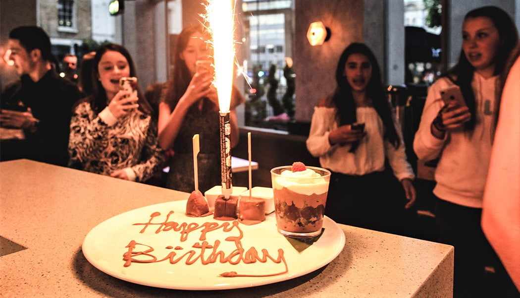 group of young women celebrate birthday party with large cake and sparkler