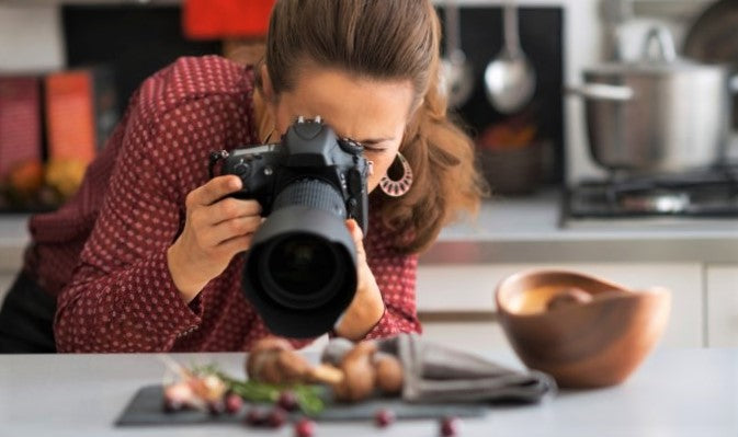 woman photographs exciting restaurant dish with dslr camera