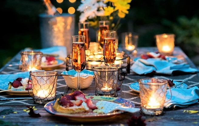 elegant restaurant dining table lit by candles and laid with champagne flutes