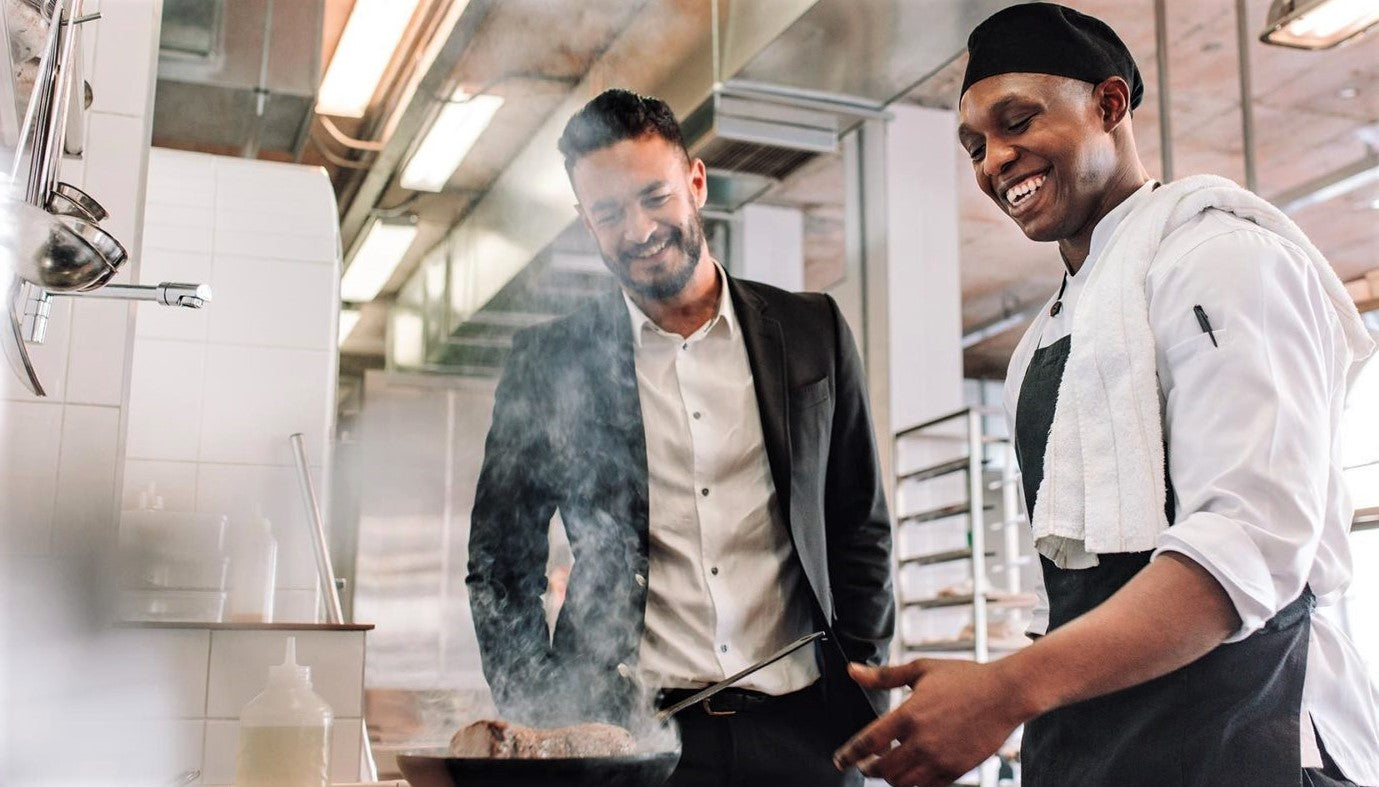 friendly hands-on manager shares conversation with happy chef in restaurant