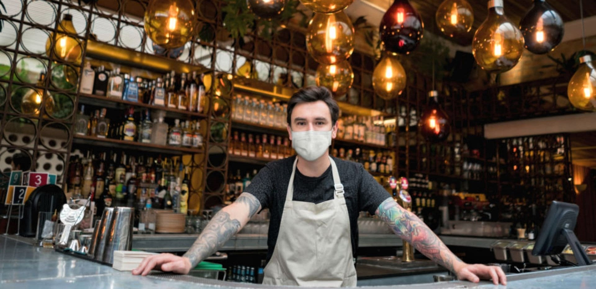 barman in face mask stands behind bar in newly reopened restaurant