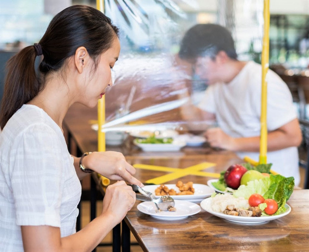 woman eats in asian restaurant with plastic barrier between her and other diner