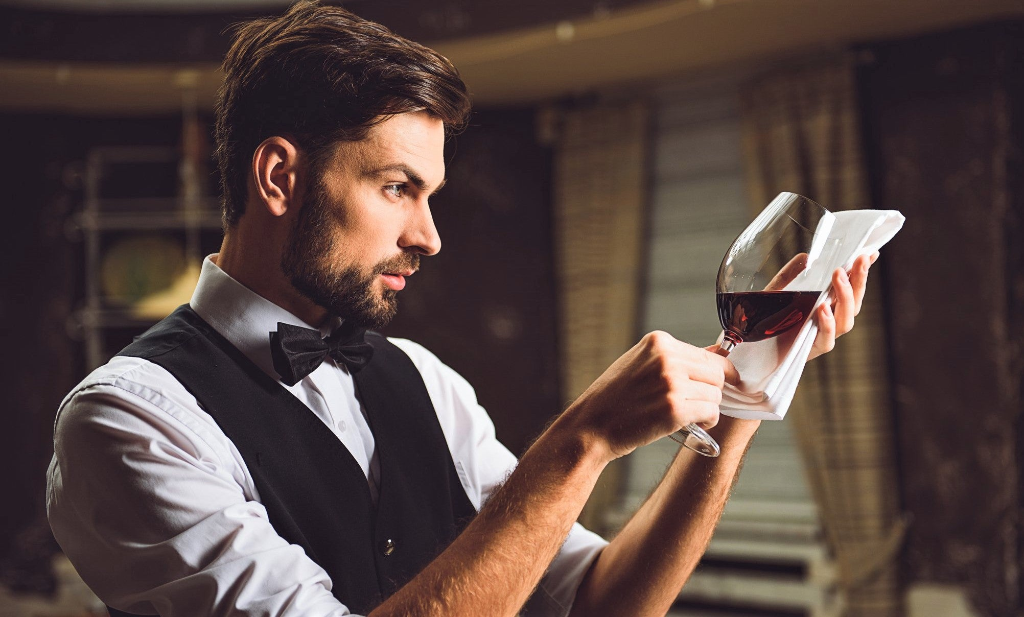 sommelier in white shirt and black waistcoat inspects glass of red wine