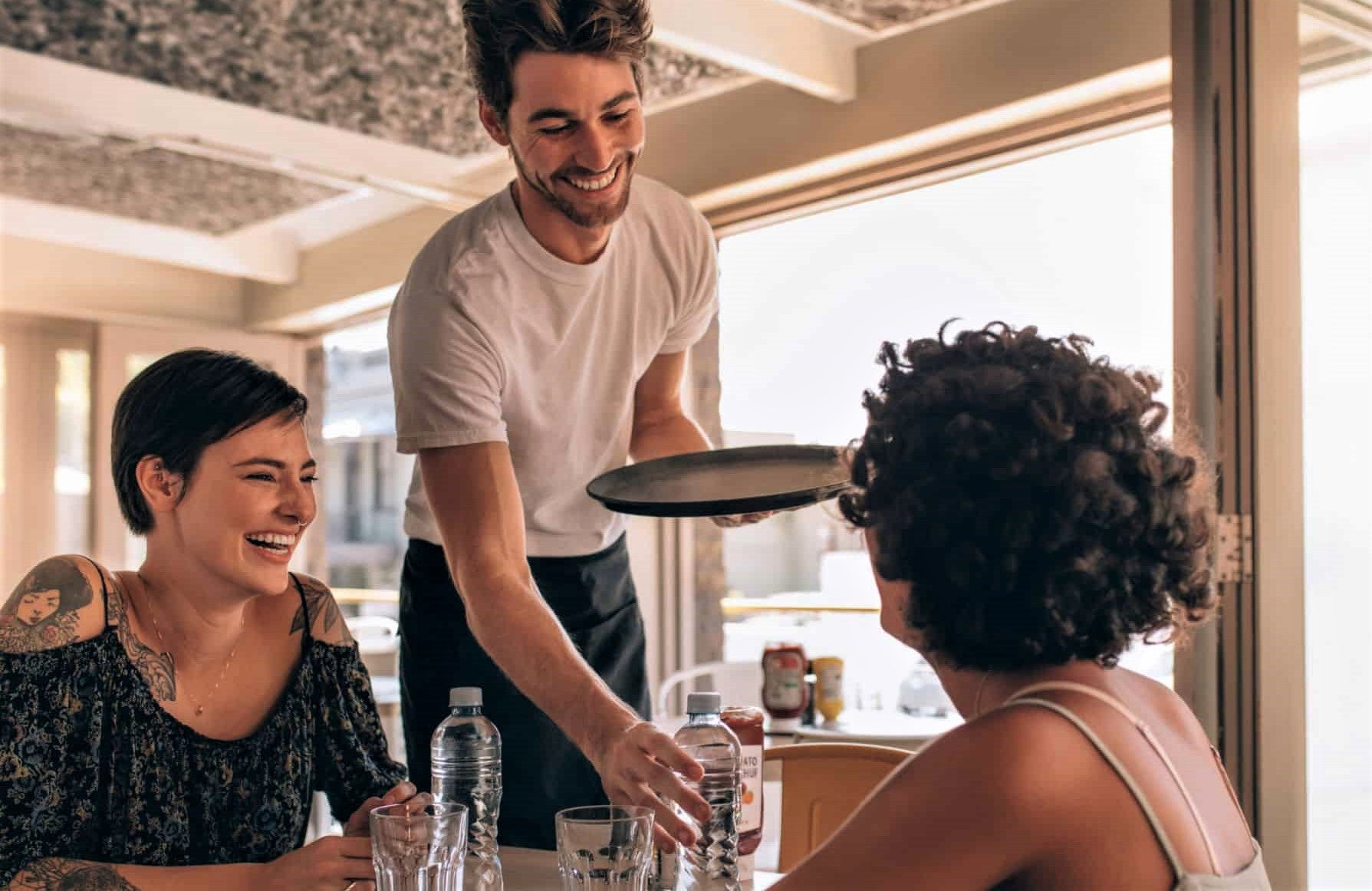attractive young waiter in t-shirt serves two women drink at restaurant table