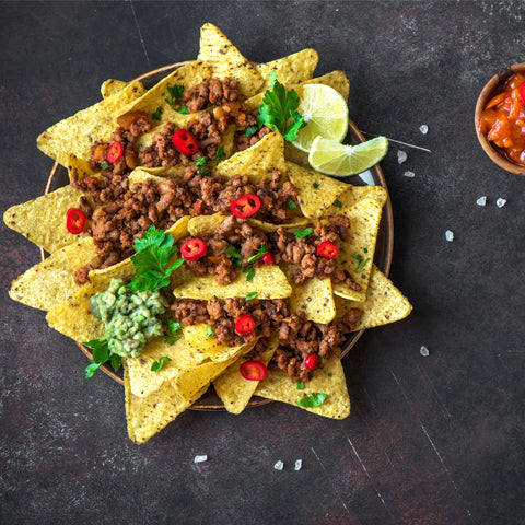 Mexican nacho corn tortilla chips with cheese, ground beef , guacamole and red hot spicy salsa