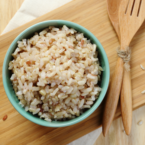 a bowl of cooked long grain brown rice, set on a wooden board, next to a wooden cooking spoon.