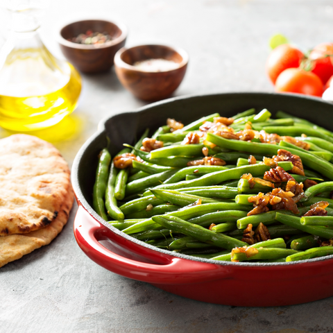 Whole Green beans cooked in a pot with nuts on top