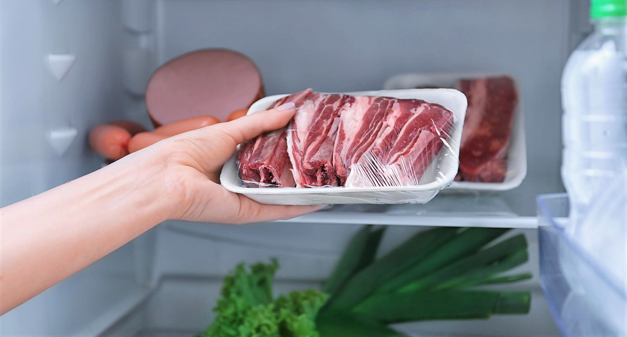 person's hand reaching into fridge pulls out packet of meat