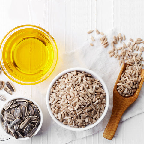 sunflower seeds peeled in a bowl next to unpeeled sunflower seeds and sunflower oil in a dish, top view