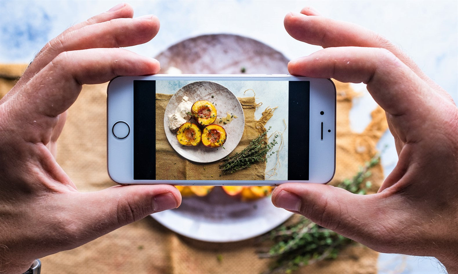 man uses iphone to photograph dish to promote favorite restaurant