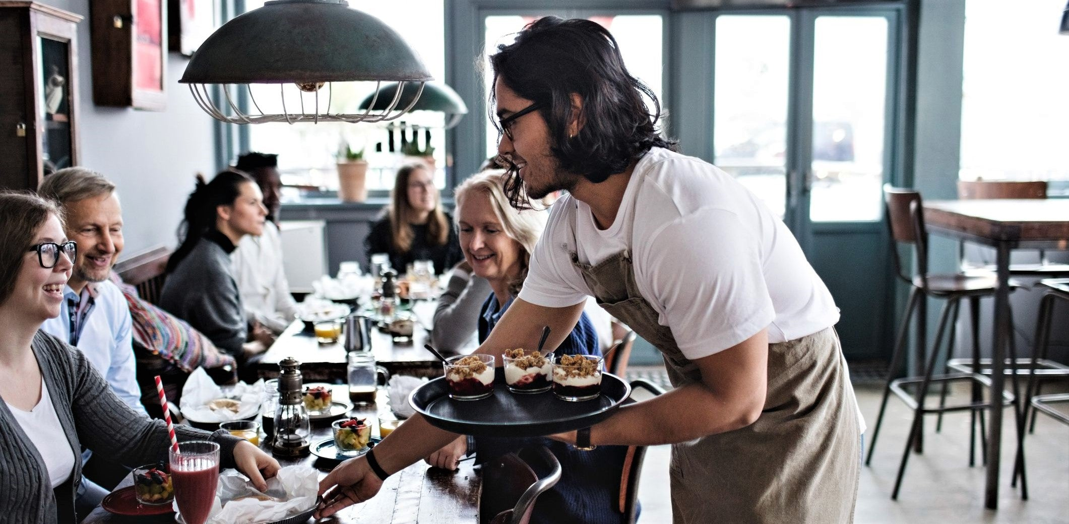 attractive young waiter with long hair and glasses delivers tray of desserts to table of smiling repeat customers
