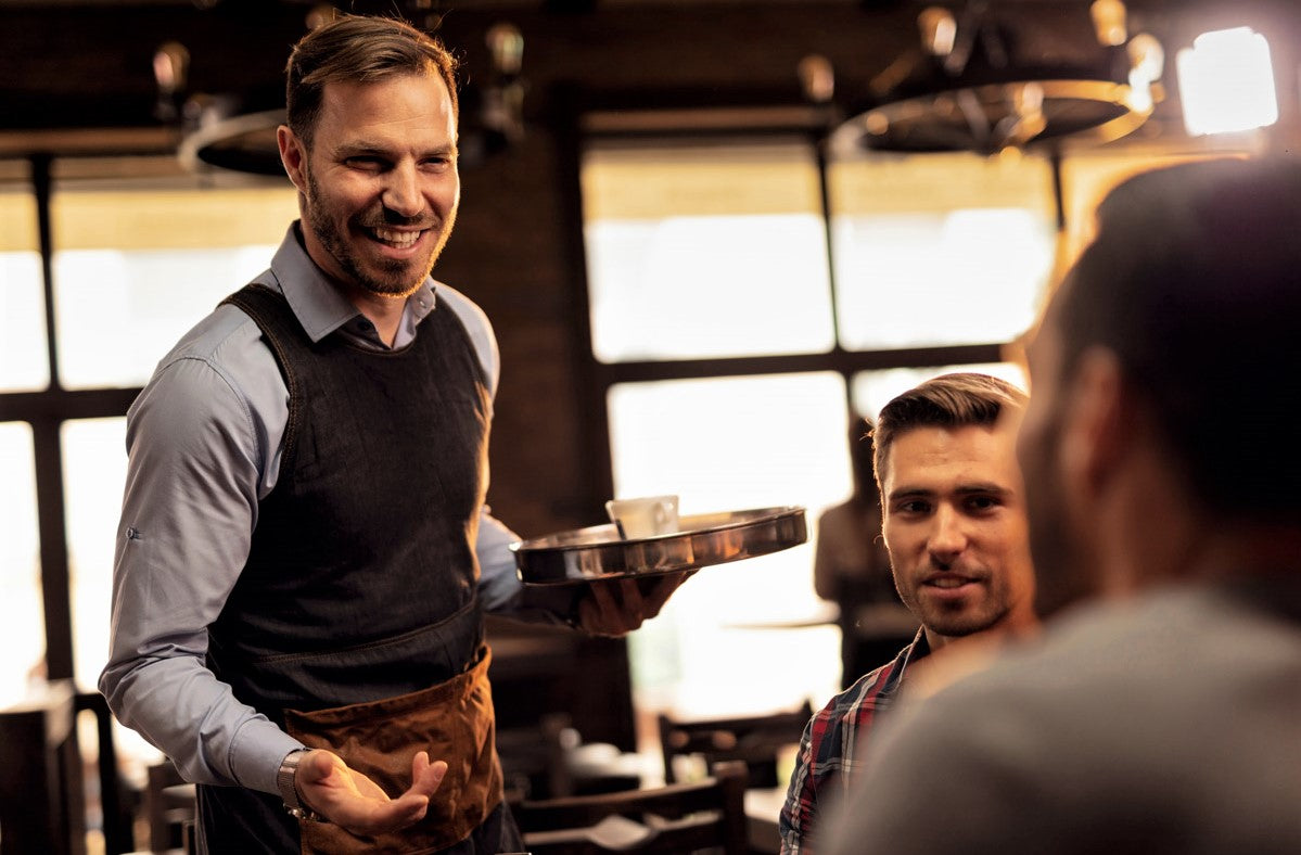 handsome male waiter in vest and button-down shirt makes recommendations to repeat customers