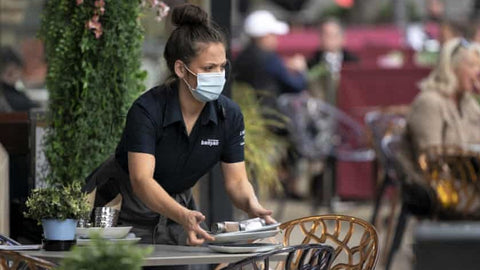waitress in face mask clears table in outdoor patio of restaurant during covid crisis