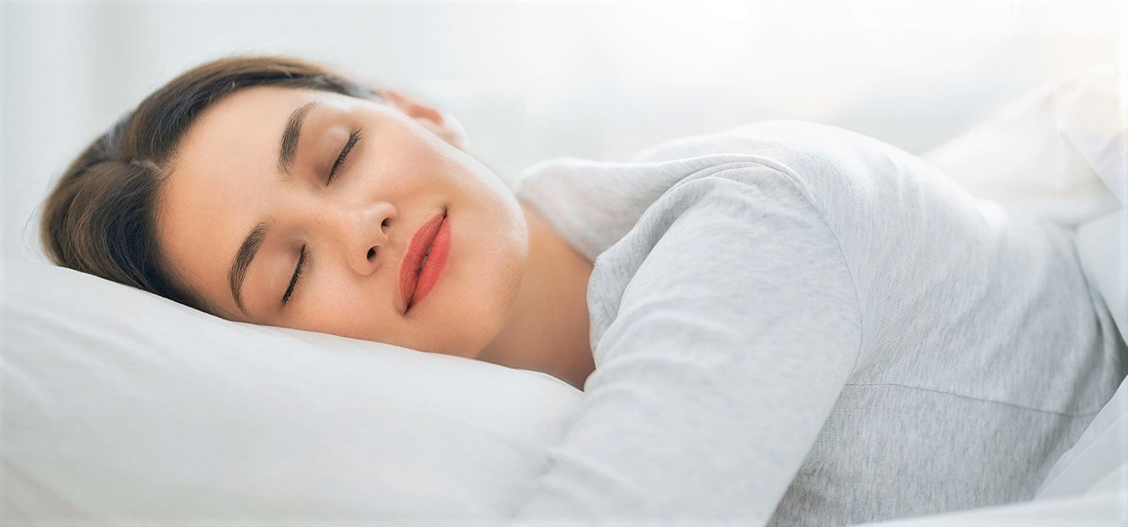 woman sleeps peacefully in bed while hugging pillow