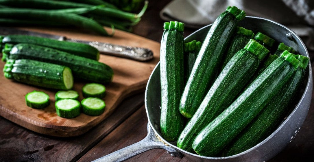 collection of fresh zucchini plants in strainer and on chopping board