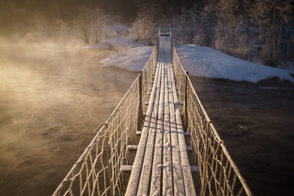 snowy and icy bridge over river