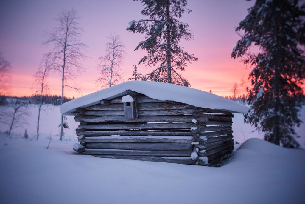 colorful sunset behind log cabin in snow
