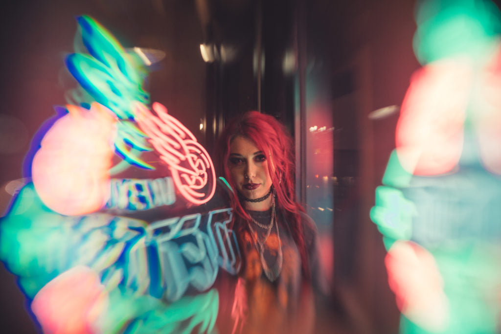 Woman with red hair in between neon lights
