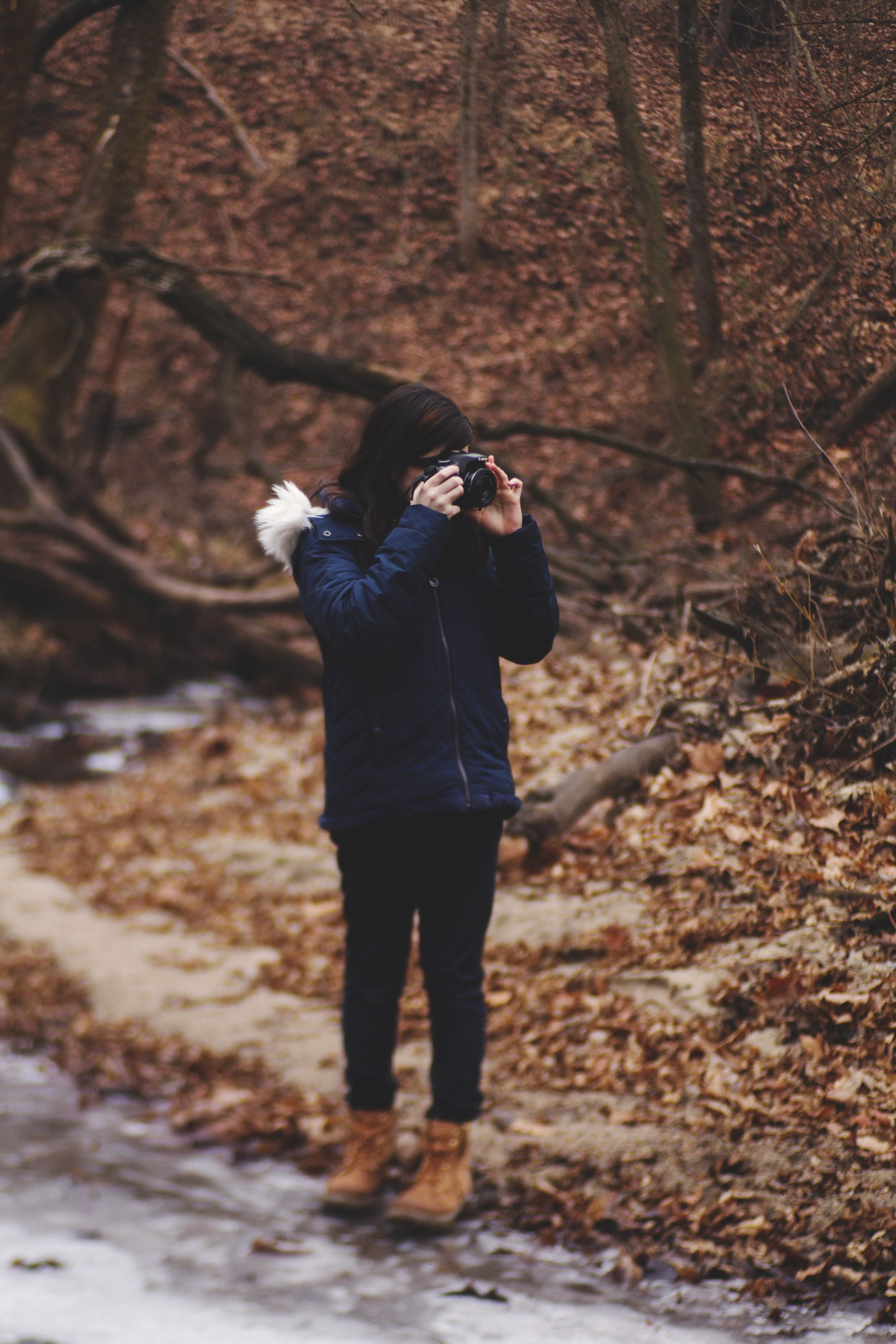Girl in navy blue jacket brown hair camera takes photos in the winter journey story amy cyphers