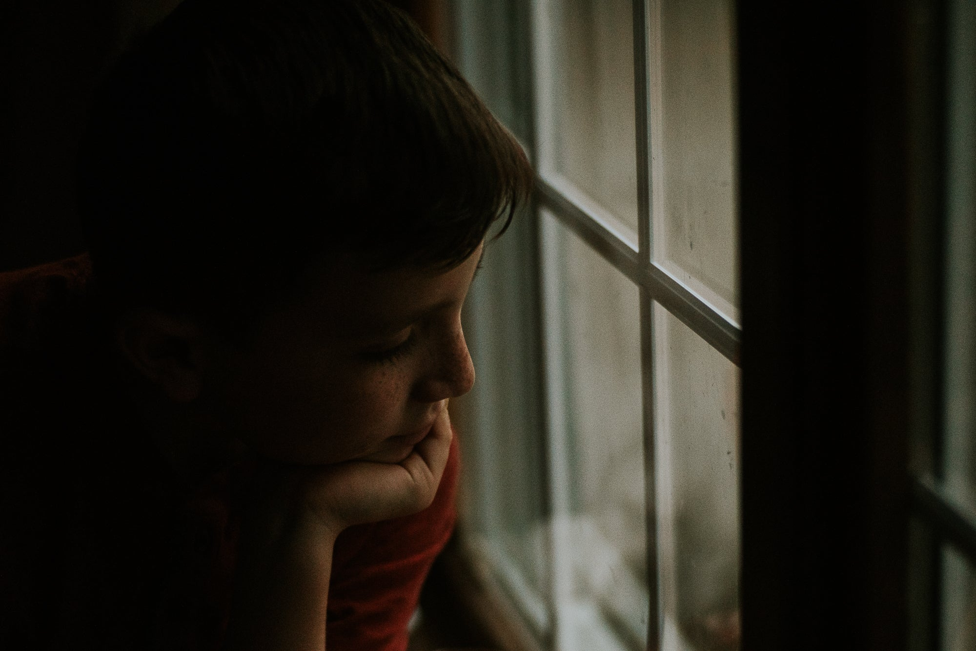 boy with freckles looks out the window with chin in hand lost look journey story amy cyphers